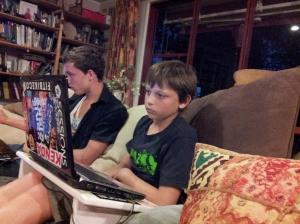 boys playing computer games sitting next to each other on sofa in living room