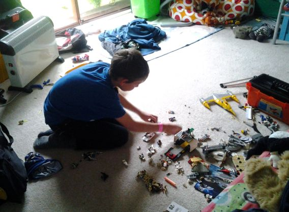 Boy playing on the floor with lego and other toys in his bedroom