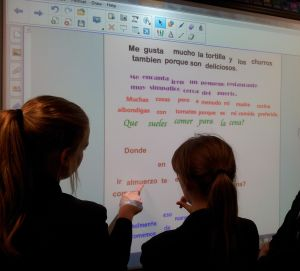 girls working together on acticity on smartboard in language classroom