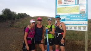 a team of four women standing in front of the trail map at the start of a trail