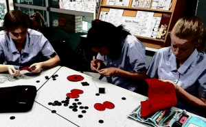 Girls making poppies out of felt in a classroom