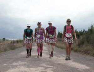 4 female walkers walking along a gravel road. cloudy sky