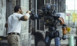 Robot high fiving a man wearing casual clothes in a  run down part of a city
