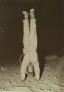 caver doing a handstand in a cave