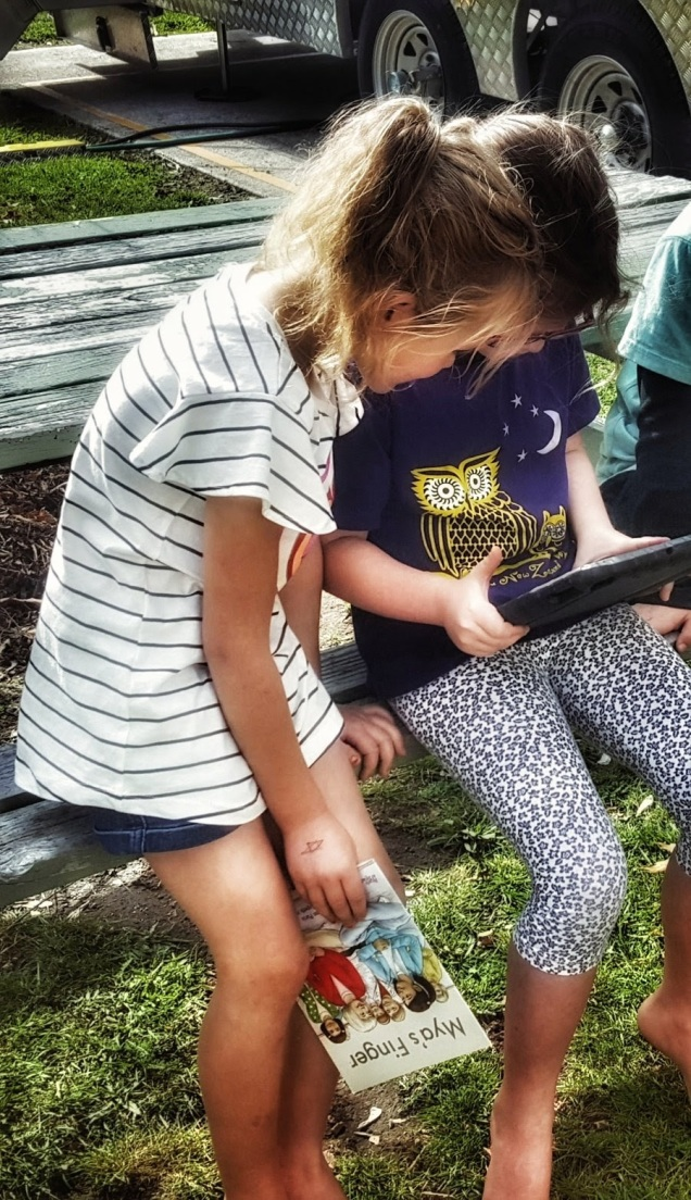 Two girls in a school yard collaborating on a project using an ipad